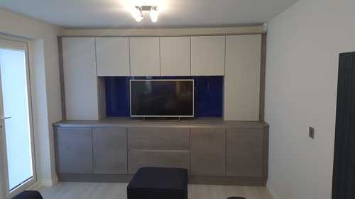 Image of a modern concrete kitchen design that extends into the living room, featuring a concrete TV unit.