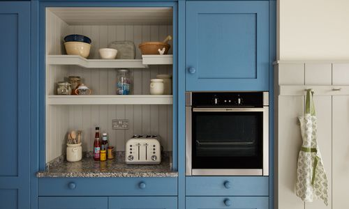 Close up image of a kitchen storage unit with an integrated oven appliance.
