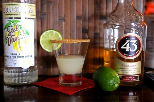 bottle of stoli vanilla and licor 43 and a key  lime pie shot with graham cracker crust rim and fresh lime garnish