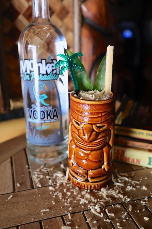 bottle of monkey in paradise vodka with a bang the tree cocktail in an authentic tiki mug