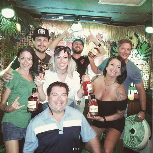 group of bartenders at tiki house during iron bartender competition posing with rum bottles