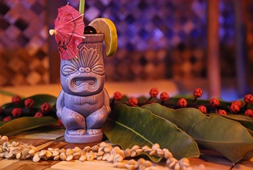 blue tiki mug with pink umbrella and fruit garnish
