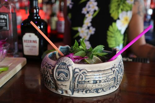 tiki cocktail in a bowl to share with two straws and fresh fruit and herb garnish