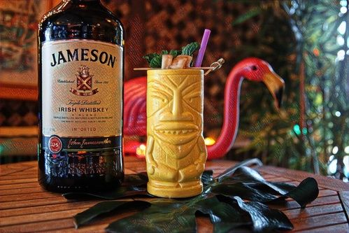 jameson whiskey bottle next to yellow tiki mug with fruit garnish