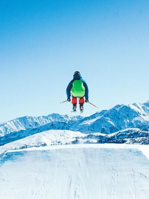 Skier Jumping In Air With Mountains Ahead.