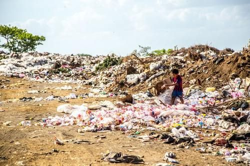 Boy At Trash Pile In India.