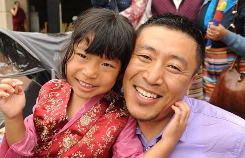 A man holding a young female child smiling.