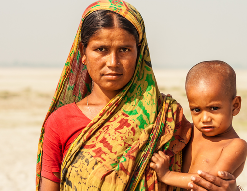 A photo of a Bangladeshi family of four. The father is holding the son, and the mother is holding a sleeping infant.