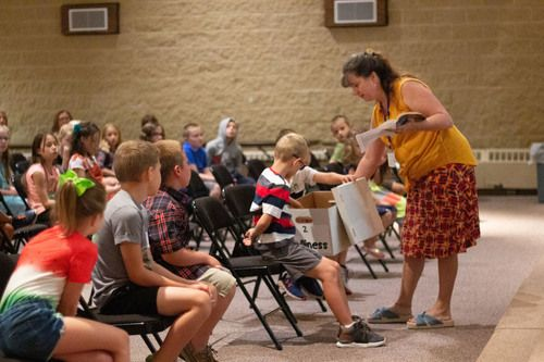 classroom with teacher in yellow shirt and patterned skirt interacting with children