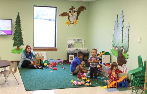 Toddlers in a classroom with green carpet and a woodland mural