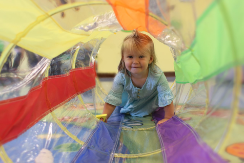 Little girl in blue dress crawling through rainbow colored tube
