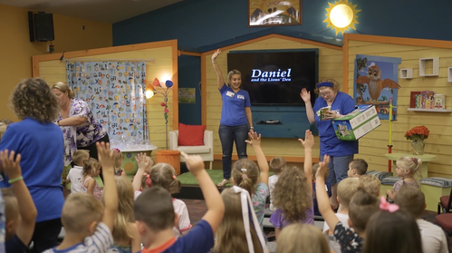 Colorful classroom with teachers in blue shirts interacting with children