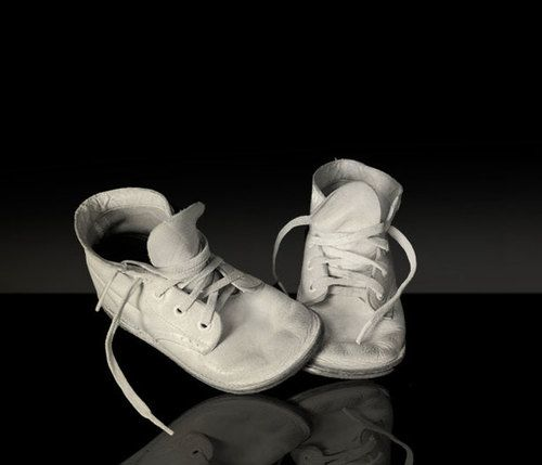 Photo of white baby shoes on black background.