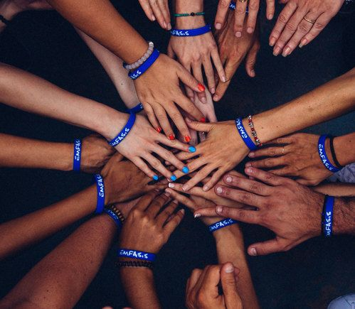 Overhead photo of many hands placed on top of each other like a team huddle.