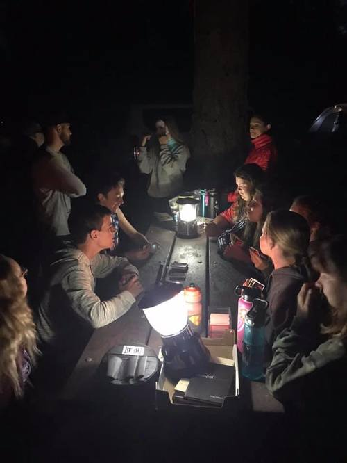 Photo of youth talking at night around a table with lanterns.