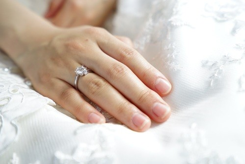 Bride's hand on a white wedding dress with a beautiful engagement ring