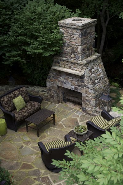 Outdoor fireplace and stone patio built by Landvision Designs