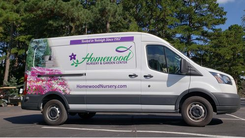 The delivery van for Homewood Nursery parked in the parking lot under the pine trees