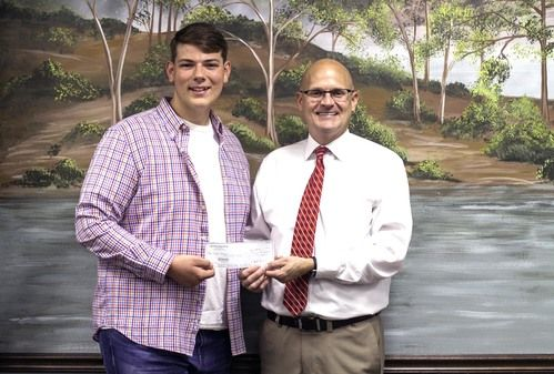 Michael Ford presenting Tyler Hoskins with his scholarship check.